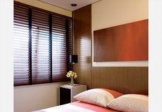 Os painéis verticais vão até o teto nas laterais da cama, criando simetria e sensação de pé-direito alto. A luminária pendente não rouba espaço na mesa lateral