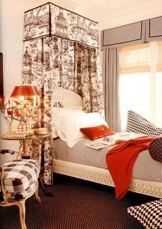 Nice mix of black and white fabrics with a pop of orange.  They did a great job with keeping the pattern on the bed canopy and using a simple color on the drapes.  I like that both valances are the same style.  Everything is perfect in this black touile draped bedroom.  Fun big checks on the chair.