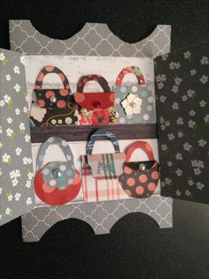 Mini paper handbags on the shelves on a dresser shaped card.