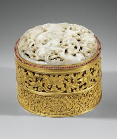 A FINE AND RARE GILT-BRONZE TIERED BOX AND COVER SET WITH A FINELY CARVED AND RETICULATED JADE PLAQUE, QING DYNASTY, QIANLONG PERIOD, Acquired in China in the early 1900s. Thence in the family by descent.