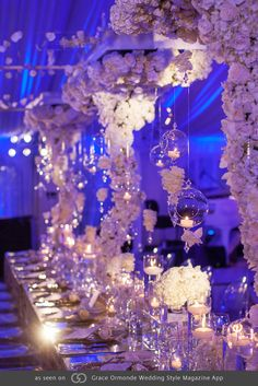 Custom designed Thomas lampshades wrapped in a shantung fabric and dressed with an upside-down and spiraling white floral trunk of white orchids, hydrangea, roses and amaryllis. Mirror tabletops reflect lush monochromatic flowers and reflective candles. @grace_ormonde @wedding_style