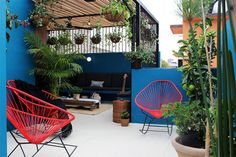 Simple but creative outdoor space/patio/courtyard with blue walls and red wire chairs. By: NINA SAND