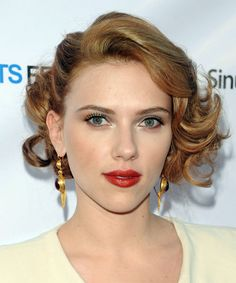 Short, curly, formal style - Description Scarlett looked like she stepped out of the 1940s with this breathtaking hairdo. To achieve her look, her hair was set in hot rollers and pinned over to one side to add body through the top and to show movement through her ends.
