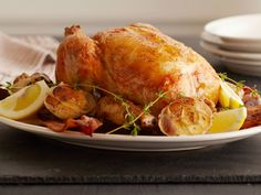 Lemon and Garlic Roast Chicken : Ina Garten dresses up her classic roast chicken by baking it with bacon on top. Then she adds a head of garlic and a sliced lemon to the roasting pan to flavor the sauce.