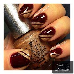 Maroon and gold nails.