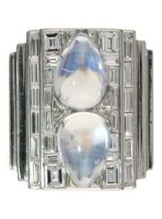An Art Deco platinum, moonstone and diamond ring. Set to the centre with two pear-shaped moonstone cabochons, surrounded by baguette diamonds, mounted in platinum. #ArtDeco #ring