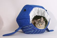 """It's just funny to see your cat inside the mouth of a giant marine mammal, and that's why The Cat Ball created the Blue Whale Cat Ball® cat bed. The Blue Whale features a lining of pretty sea turtles and a """"baleen"""" fringe that cats like to rub their heads on."""