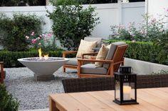 Terrasse mit Kiesboden und Holzmöbeln.