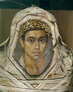 Mummy with an Inserted Panel Portrait of a Youth Period: Roman Period Date: A.D. 80–100 Geography: Country of Origin Egypt, Fayum, Hawara (Hawwara, Hawwaret el-Maqta; Adlan), Petrie Medium: Encaustic on limewood, linen, human remains