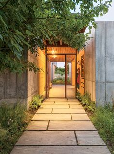 A palette of stone, concrete, and greenery greets guests at the home's front entrance.