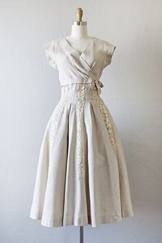 1950s Carlye cream linen party dress. Vintage 50s dress features wrap style bodice, short dolman sleeves with gussets, and dark cream colored lace panels all along the skirt and inverted pleats from the hips that creates a flattering fit and flare shape on the figure.