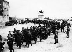 Several hundred German prisoners passing by the equestrian statue of Napoleon at Cherbourg. June 1944.