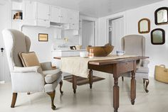 We love how the upholstered wing chairs in this breakfast nook add a bit of living room luxury.     Check out more of this house -- that's actually a renovated blacksmith shop! http://www.countryliving.com/homes/house-tours/white-room-decorating-ideas