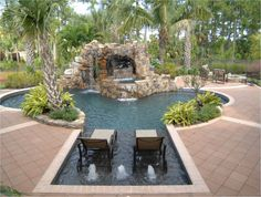 Master Pools Guild | Residential Pools and Spas - Freeform Gallery - maybe this shape, without the extravagant tower/waterfall/grotto feature...?  Like the sun deck, planters with tropical plants alongside pool, uninterrupted swim lane