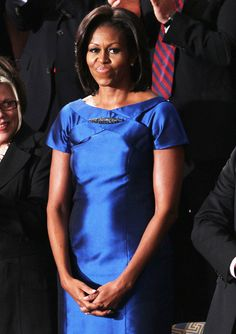 Michelle Obama wore a sapphire blue dress by Barbara Tfank accessorized with an Alexis Bittar brooch.