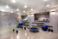 This modern house has a multi-purpose room that's been set up as a gym. A mirrored wall for when working out, or when relaxing, someone can cozy up in the raised day bed that's built into the wall. #HomeGym #BuiltInDayBed