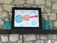 2017   This year we decorated the mantle with vintage-inspired, turquoise bottles filled with daisies and placed them on either side of a framed poster of  our custom event logo.