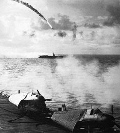 JAPANESE DIVE BOMBER PLUNGING TOWARD THE SEA, downed by antiaircraft fire from a Navy carrier during the Battle of the Philippine Sea, which started on 19 June. Aircraft in the foreground are Grumman Avengers (TBF-1 torpedo bombers). A Japanese naval force approaching the Marianas caused U.S. ships at Saipan, except for those unloading the most necessary supplies, to withdraw to the east. Troops ashore were left without naval gunfire, air support, or sufficient supplies.