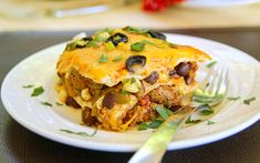 30 Minute Simple Mexican Lasagna - lean ground beef - olive oil - small yellow onion - smoked paprika - cumin - chili powder - kosher salt - 14/5 oz. can diced tomatoes - 14 oz. can black beans - frozen corn - 4 oz. can fire roasted diced green chilies - 10 oz. can enchilada sauce - large flour tortillas - Mexican cheese blend - black olives - scallions - cilantro