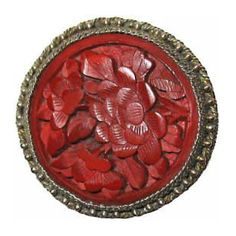 Late 19th or early 20th century carved cinnabar button in silver filigree collet. Cinnabar is a crimson-colored lacquer from China. Many of these were imported during the oriental craze of the 20's.