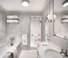 The master bath's mirrored walls were replaced with slabs of crema delicato marble; the sink and tub are by Kohler, with fittings by Dornbracht, the sconce is by Marvin Alexander, and the towels are by Leontine Linens.