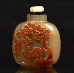 CHINE - XIXe siècle  Flacon tabatière de forme carrée en agate sculptée en haut relief dans la veine brune d'un daim, oiseau, abeille, singe sous un pin.  Bouchon en jadéite.