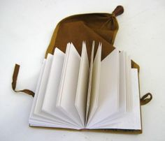 """Make a Girdle Book. In this workshop students will create a medieval style leather """"girdle book"""". These books were worn by monks, nobles and women in medieval times. The long tapered tail at the end of the book was slipped through the belt or girdle, and the knot/knob at the end stopped the book from coming off. The book hangs upside down, for easy reading while still on one's belt or girdle."""