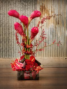 This exotic red centerpiece is from Tony Foss Flowers. Click to see what types of flowers were used! Photo by Andrea Murphy Photography. #centerpiece #flowers #wedding #decor #weddingreception