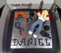 A gym junkie themed cake created by Shandi Sansom from Sugar Kissed. Featuring a hand crafted gym dude on a bench pressing weights, a skipping rope, duffel bag and hand weights. Please visit my facebook page to see more of my work: www.facebook.com/sugarkissedshandi
