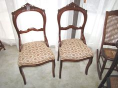 """Seven antique and vintage chairs including two Victorian walnut chairs with carved backs and upholstered seats, 37""""T; an antique petite sewing rocker with cane seat and back; an unfinished maple rocking chair, 44""""T; three 19th century dining room chairs with painted backs, two have cane seats, one has a wooden seat."""