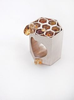 'Ooze': a silver and glass ring in the form of a honeycomb by Kristen Baird; honey is a symbol of natural sweetness. (behance.net)