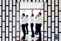 Taking inspiration from the powerful graphic lines of the foreground wall, the photographer devised an equally graphic posing strategy for the groom and his attendants. The symmetry and subtle pops of color in a field of mostly black and white provides a strong, masculine feel—but with just enough humor to keep it lighthearted.