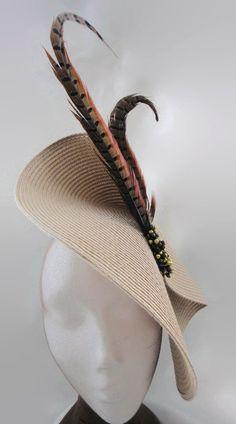 Tocado gris topo adornado con plumas de faisan sujetas con adorno realizado a mano en tonos dorado y marrón. El tocado se sostiene sobre diadema.  Puede