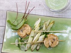 These salmon skewers are served with sorrel cream over a bed of asparagus.