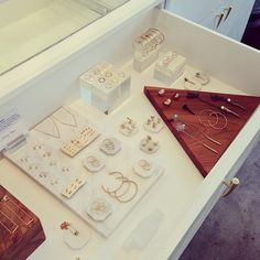 Cool display with jewelry laid out - set of drawers with glass top.