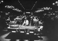 "Caption that accompanied image in LIFE in 1955: ""Idling croupiers (in shirtsleeves) dawdled behind their roulette tables because few customers were placing bets in The Dunes two weeks after opening night. Business was as bad on the 120 nickel-to-silver dollar slot machines banked around the room of the new club's gambling casino."""