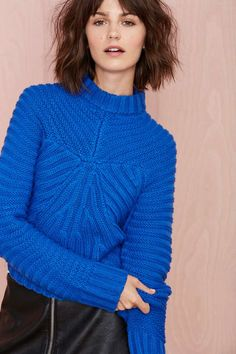 Meet us in the middle with this blue cable knit crop sweater featuring a mock neck, rounded hem, and ribbing at cuffs.