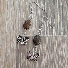 Oorbellen van ovale bronziet met metalen vlinders. Van JuudsBoetiek, te bestellen op  www.juudsboetiek.nl.