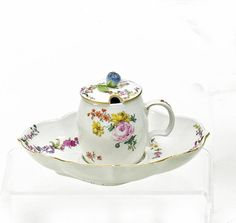 Mustard Dish and Saucer with Fine Floral Decor.   Meissen. 2nd half 18th C.     Porcelain, enriched with colours. Gold edging. Height 9cm/ 3,5x17,5x13,5cm. Inner edge of the lid has been restored.   Crossed swords mark. Saucer with press number 30.