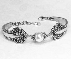 This intricately detailed antique spoon bracelet was created from two silverplated teaspoons. The pattern is the beautiful Avon from 1901. These spoons were a great find, as due to their age and popularity, its hard to find them in both nice condition and at a decent price. The bracelet is adorned with a 10mm white Swarovski crystal pearl, secured within two Bali sterling silver bead caps and twists of sterling silver wire. The spoon bracelet is finished with an Italian sterling silver…