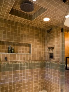 This master bathroom features a custom-designed shower with a frameless enclosure, floor-to-ceiling intricate hand-painted tile with accent banding, a built-in niche, a 12-inch rain showerhead and oil-rubbed-bronze plumbing hardware.