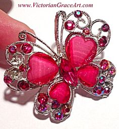 AB Fuschia-red rhinestone butterfly brooch with heart shaped lucite wings with slight sparkle.