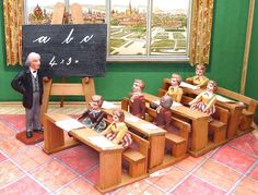 German school set from the Erzgebirge, ca. 1920.  There are 4 school desks, 7 students, 1 frame with a blackboard and the teacher. The students have moveable arms and legs.   They are all approximately 6 to 6.5 cm in size. The teacher is formally dressed in long coat, suit an tie.