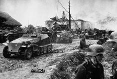 """Tropas alemanas mecanizadas en Stariz recién evacuada por los rusos, antes de continuar la lucha por Kiev. Los edificios al fondo dan testimonio de la rigurosidad de la política de """"tierra quemada"""" llevada a cabo por los rusos,  Rusia el 21 de Noviembre de 1941."""