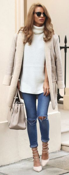 Nada Adelle wears a pale shearling lined coat with denim jeans and a pair of beige lace up heels.   Shealring Lined Coat: New Look, Sleeveless Knit: Ark, Jeans: Asos, Heels: Fashion Nova.