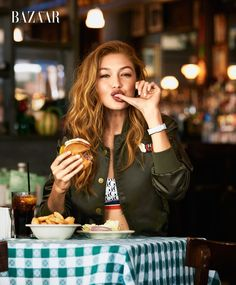 Gigi Hadid wears Tommy Hilfiger x Gigi bomber jacket and bralette More