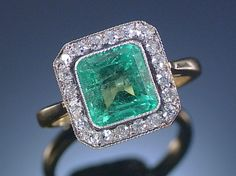 EMERALD AND DIAMOND RING, EARLY 20TH CENTURY. Designed as a square plaque centring on a millegrain collet-set step-cut emerald within circular-cut diamond surrounds