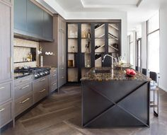 Exquisite contemporary black and brown kitchen features a black island accented with an x-trim and a gold and black marble countertop seating curved blue leather counter stools placed on large brown herringbone floor tiles.
