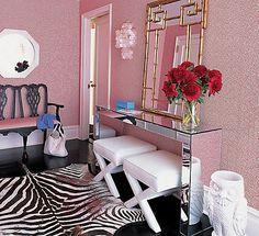 Quarto feminino chiquérrimo, com tapete no estilo animal print, papel de parede rosa, um belíssimo espelho de moldura dourada e dois belos pufes com pés em x, sob o aparador espelhado. #interiorstyling #interiordecor #peçaslindas #quarto #quartofeminino #puffs #pufes #decoraçãodebomgosto #decoraçãoelegante #decorfeminina #penduradores #decoraçãodeinteriores #designdeinteriores #decorarfazbem #comprardecoracao #carrodemola.