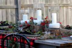 use slices of wood as candle bases on a sanded plank table with a vivid plaid blanket for a tablecloth